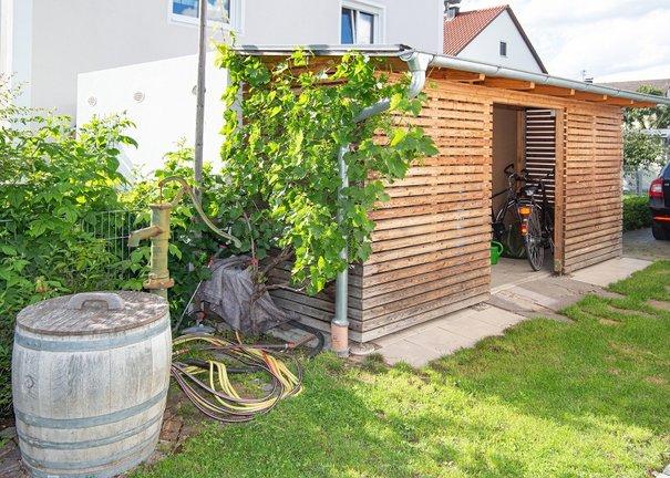 Holzlege und Gartenbrunnen